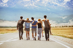 Happy travel friends road concept. Group of five happy friends going ahead on straight road. Space for text Royalty Free Stock Image
