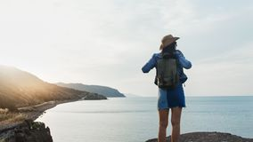 Happy travel hipster female having positive emotion raising hand looking on seascape at sunset. Back view. Pleasant backpacker tourist woman having fun stock video footage