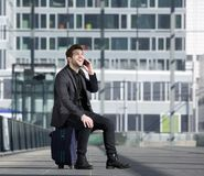 Happy travel man talking on mobile phone while sitting on suitcase Stock Photography