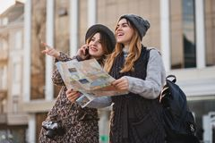 Happy travel together of two fashionable girls in sunny city centre. Young joyful women expressing positivity, using map. Vacation with bags, camera, making royalty free stock photos