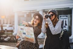 Happy travel together of two fashionable girls in sunny city centre. Young joyful women expressing positivity, using map. Vacation with bags, camera, making royalty free stock photo