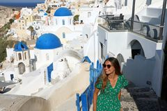 Happy travel tourist woman go upstairs in Santorini, Greek Islands, Greece, Europe. Girl on summer vacation visiting famous royalty free stock images