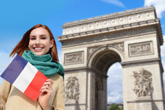 Happy travel woman in Paris. Happy woman travel in Paris, Arc de Triomphe and holding France French flag, caucasian beauty Stock Image