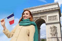 Happy travel woman in Paris. Happy woman travel in Paris, Arc de Triomphe and holding France French flag, caucasian beauty Royalty Free Stock Photography