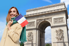 Happy travel woman in Paris. Happy woman travel in Paris, Arc de Triomphe and holding France French flag, caucasian beauty Royalty Free Stock Photo