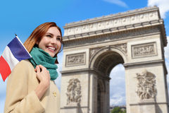 Happy travel woman in Paris. Happy woman travel in Paris, Arc de Triomphe and holding France French flag, caucasian beauty Royalty Free Stock Images