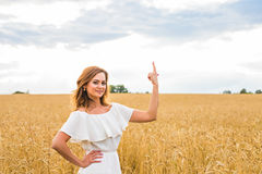 Happy travel woman smile to you and show something by finger with sky background, caucasian beauty.  Royalty Free Stock Photos