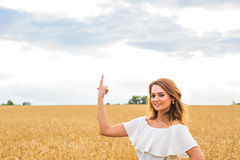Happy travel woman smile to you and show something by finger with sky background, caucasian beauty.  Royalty Free Stock Images