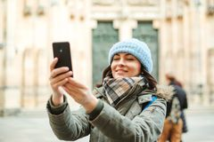 Happy travel woman taking photo with her phone. Autumn or winter trip. Young woman in warm clothes enjoying journey in Europe. Peo. Ple, lifestyle and travel royalty free stock photography