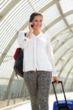 Happy travel woman talking on mobile phone at train station Stock Photos
