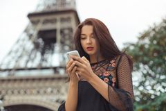Travel woman using smartphone near the Eiffel tower and carousel, Paris. Happy travel woman using smartphone near the Eiffel tower and carousel, Paris. Portrait Stock Images