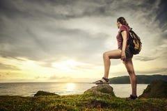 Happy traveler with backpack enjoying sunset view. Happy traveler with backpack standing on top of a mountain and enjoying sunset view. Island Lombok. Indonesia stock images