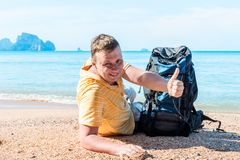 Happy traveler with a backpack got to the sea. Portrait on the beach Royalty Free Stock Photography