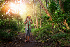 Happy traveler with backpack hiking in rain forest. Woman traveler with backpack walking in rain forest. Adventure, travel, tourism, hike in jungle concept royalty free stock photos