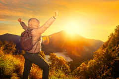 Happy traveler with backpack standing on a rock with raised hand Stock Photography