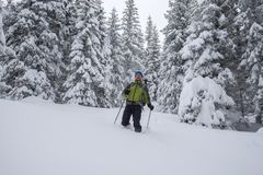 Happy traveler, with backpack, is walking in deep snow Royalty Free Stock Images