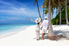 Traveler couple stands on a beautiful, tropical beach royalty free stock photography