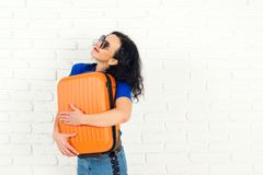 Happy traveler girl hugging her orange suitcase. Casual girl is ready to travel. Happy woman in sunglasses dreaming about vacation royalty free stock images
