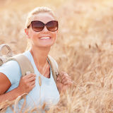 Happy traveler girl in wheat field Stock Images