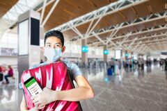 Happy traveler hugging his luggage with digital vaccine passport ready at the airport