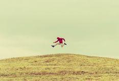 Happy traveler jumping on the hill Royalty Free Stock Photo