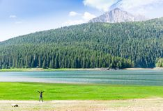 Happy traveler at lake in mountains Royalty Free Stock Photo