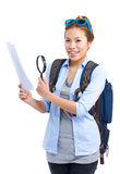 Happy traveler looking at guide with magnify glass Stock Photography