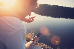 Happy traveler making selfie with mobile phone near the lake outdoors Stock Photo