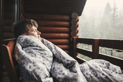 Happy traveler man resting in blanket on wooden porch with view on woods and mountains. Space for text. Hipster relaxing in. Wooden cabin in forest. Travel and royalty free stock photo