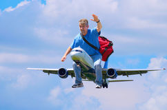 Happy traveler traveling man riding airplane. A happy man with a red duffel bag is waving as he flies through the air riding on an airplane like someone would stock photos