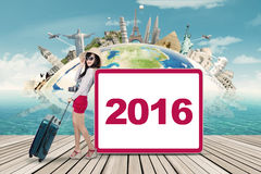 Happy traveler and number 2016 on the board Stock Photos