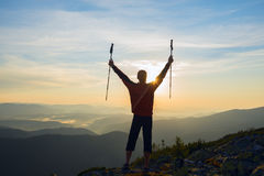 Happy traveler, with open arms, stands on the edge of the cliff Royalty Free Stock Photo