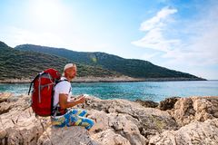 Happy traveler with a portable solar battery attached to his backpack royalty free stock photo