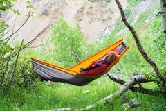 Happy traveler is relaxing in hammock stock photos