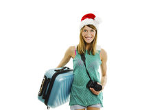 Happy traveler in santa hat with camera and suitcase going on vacation. Royalty Free Stock Photography