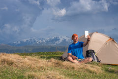 Happy traveler sit next to tent and taking selfie Stock Images