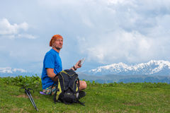 Happy traveler sits on the alpine meadow with a tablet computer Stock Photos