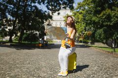 Happy traveler tourist woman in yellow clothes, hat sitting on suitcase holding city map search route in city outdoor. Girl traveling abroad to travel on royalty free stock image