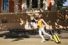 Happy traveler tourist woman in yellow summer casual clothes, hat with suitcase city map running jumping in city outdoor. Girl traveling abroad to travel on stock image