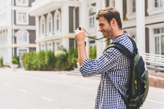 Happy traveler using camera in town Stock Photos