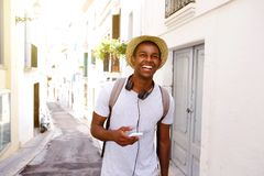 Happy traveler walking in town with mobile phone and bag Royalty Free Stock Image