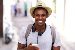 Happy traveler walking in town with mobile phone Royalty Free Stock Photography