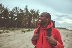 Happy traveler wearing backpack and looking around royalty free stock image