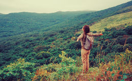 Happy traveler woman standing in the mountains. Freedom happy traveler woman standing with raised arms and enjoying a beautiful nature. Image with instagram Stock Photos