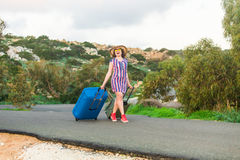 Happy traveler woman with suitcase on the beach. Concept of travel, journey, trip.  royalty free stock images