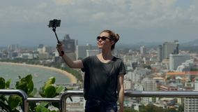 Happy traveler woman is taking photo. Young girl take selfie with phone and stick on summer city. Urban life concept. Happy traveler woman is taking photo stock video footage