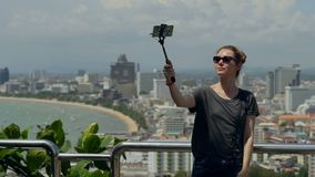 Happy traveler woman is taking photo. Young girl take selfie with phone and stick on summer city. Urban life concept. Happy traveler woman is taking photo stock footage