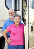 Happy Travelers. Senior couple standing in the doorway of their luxury motor home Stock Photo