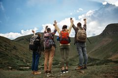 Happy travelers putting hands up after reaching the top stock photography