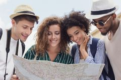 Happy travelers searching the location on city map. Happy multiracial travelers searching the location on city map royalty free stock photography